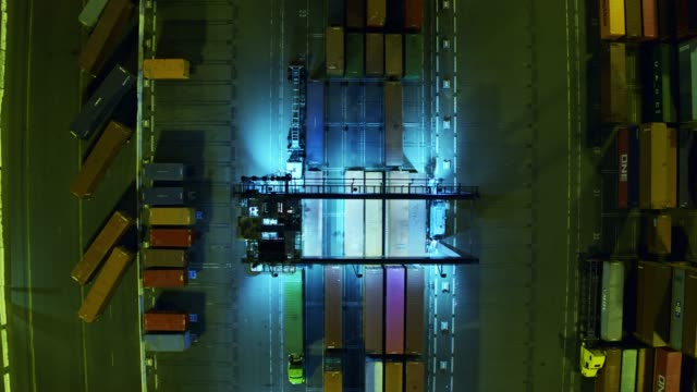 descending top down aerial view of straddle carrier moving cargo containers in port - straddle carrier stock videos & royalty-free footage