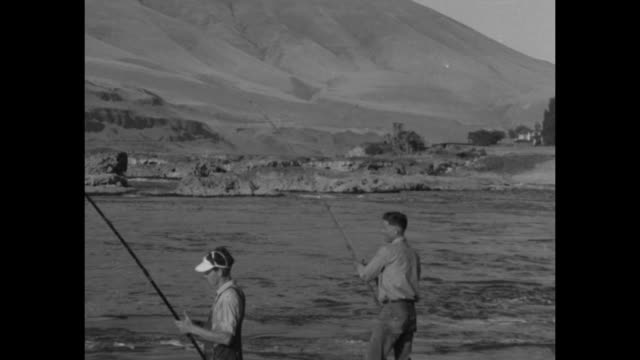 deschutes river flows near tumwater, wa / fishermen stand on shore as swift current moves past / two fishermen with rods and reels / river water /... - sample holder stock videos & royalty-free footage