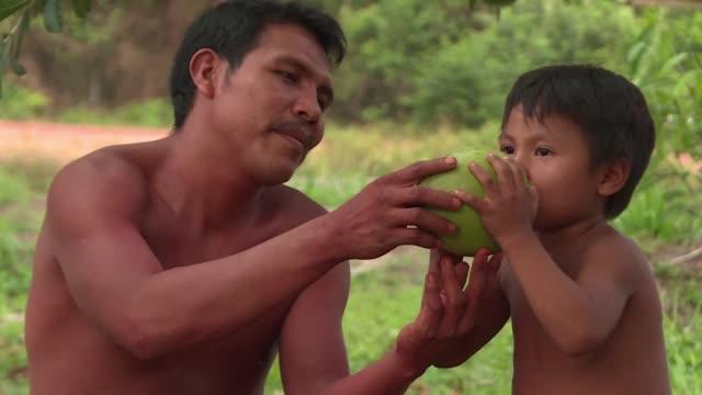 desde las profundidades de la selva amazonica brasilena un miembro de una tribu ancestral se conecta con el mundo exterior a traves de la política... - tribu sudamericana video stock e b–roll