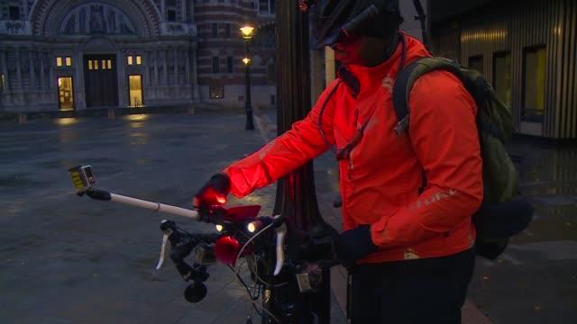 desde su bicicleta lewis saca tarjetas rojas a los automovilistas que actuan peligrosamente en el centro de londres - transporte stock videos & royalty-free footage