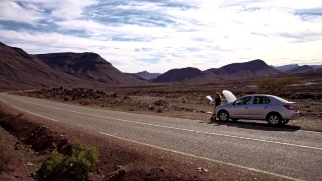 vídeos de stock e filmes b-roll de desert adventure. woman on a road trip, waiting with broken car, checking map - danificado