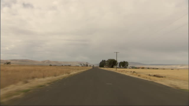 a desert highway appears as a straight, flat ribbon from the back window of a vehicle. available in hd. - shrubland stock videos & royalty-free footage