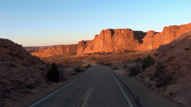 vídeos de stock, filmes e b-roll de a desert highway winds toward a mesa. - mesa formação rochosa