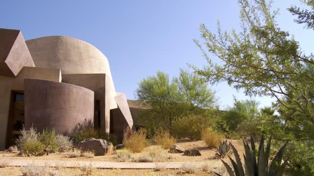 ws pan desert landscaped garden to front entrance of palm desert henderson community center / palm desert, california, usa  - コミュニティセンター点の映像素材/bロール