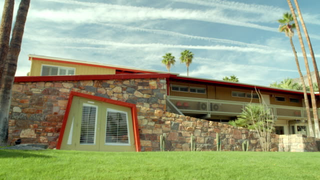 LA TS desert oasis boutique resort hotel built in 1947 featuring exterior native stone walls and an asymmetrical odd-angled entrance doorway to one of the guest rooms, long sloping roof lines and redwood sidings