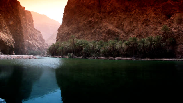 ws desert oasis in oman (wadi shab) with turquoise lake and mountains - desert oasis stock videos & royalty-free footage