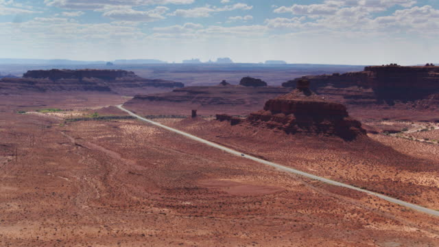 desert road with monument valley silhouetted in distance - navajo reservation stock videos and b-roll footage