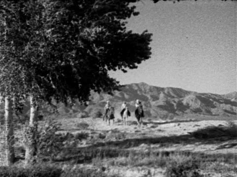 Desert scrub w/ tree FG mountains BG three horseback riders dressed in Western clothing cowboy hats on riding horses walking horses down frame out...