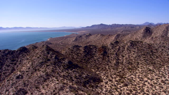 desert shrubs dot the arid coastal mountains at the shoreline of the sea of cortez in california. available in hd. - sea of cortez stock videos & royalty-free footage