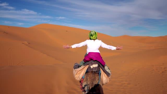 desert trip. woman enjoying ride on camel - exploration stock videos & royalty-free footage