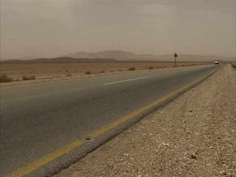 stockvideo's en b-roll-footage met desert wa shot, single car drives down empty road, syria (sound available) - tweebaansweg