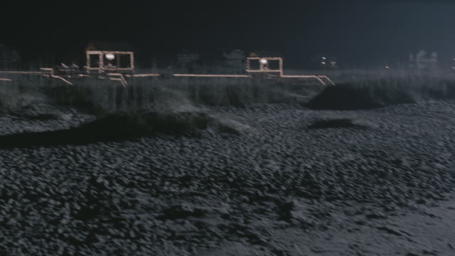 pan deserted beach at night with lights in the distance - sand dune stock videos & royalty-free footage