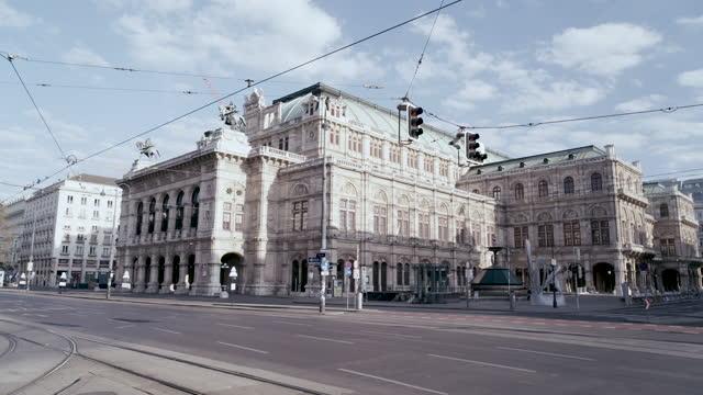 deserted state opera vienna from kärntnerring and karlsplatz in vienna, austria during the covid 19 shutdown/corona lockdown - カールスプラッツ点の映像素材/bロール
