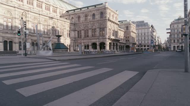 deserted state opera vienna from kärntnerstrasse and karlsplatz in vienna, austria during the covid 19 shutdown/corona lockdown - カールスプラッツ点の映像素材/bロール