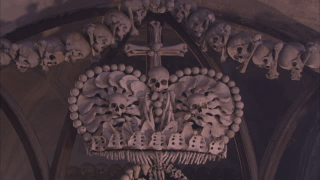 Design detail on Schwarsenberg family coat of arms made entirely from human skeletons hanging on chapel wall in the Sedec Ossuary Available in HD.
