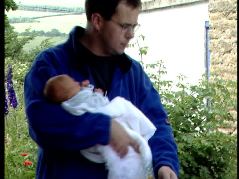 vídeos de stock e filmes b-roll de 'designer baby' jamie whitaker home from hospital; 17.25: u'lay england: derbyshire: ext jayson whitaker towards from house carrying baby jamie... - modificação genética