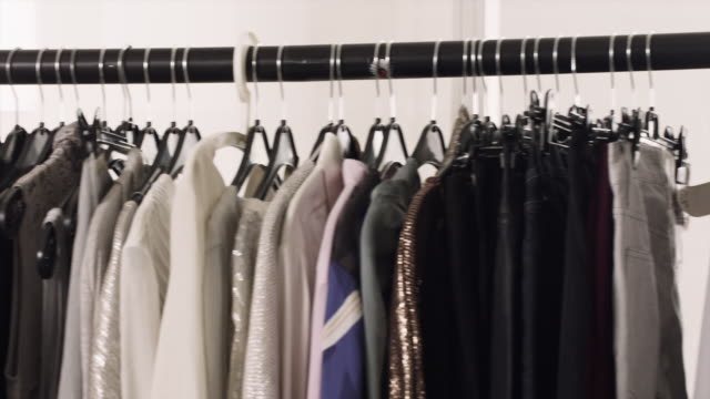 stockvideo's en b-roll-footage met designer clothes hang from a rack . - kledingrek