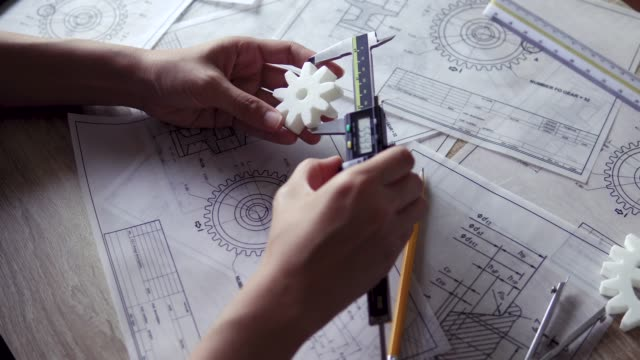 designer engineer holds 3d printed gear to inspect diameter with vernier caliper - vernier calliper stock videos & royalty-free footage