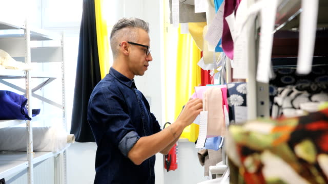 designer examining pink rolled up fabrics in rack - owner stock videos & royalty-free footage