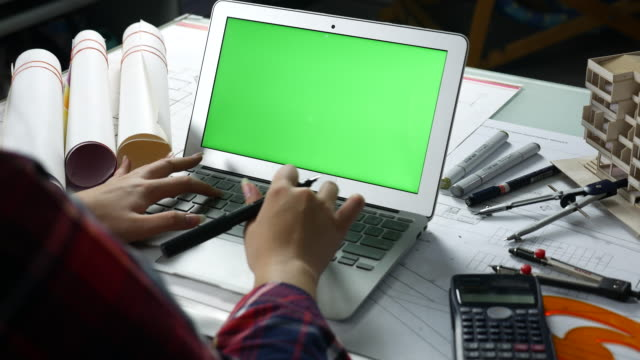 Designer using Laptop with green screen,
