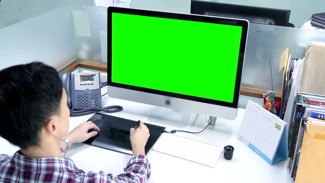 HD : Designer working with Monitor green screen [Tilt-Down]