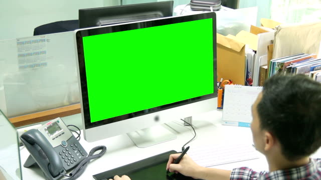 HD : Designer working with Monitor green screen [Tilt-Up]