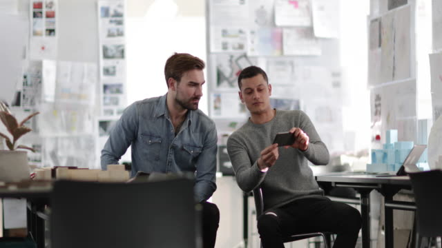 designers looking at smartphone in creative workspace - architect stock videos & royalty-free footage