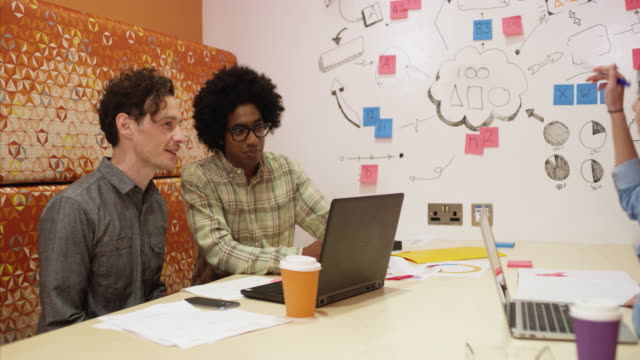 ms of designers talking and brainstorming in meeting in creative office - kooperation stock-videos und b-roll-filmmaterial