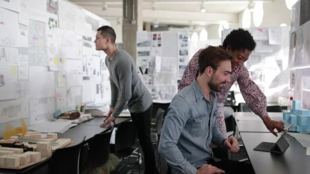 vidéos et rushes de designers working together in a creative office - panneau d'information