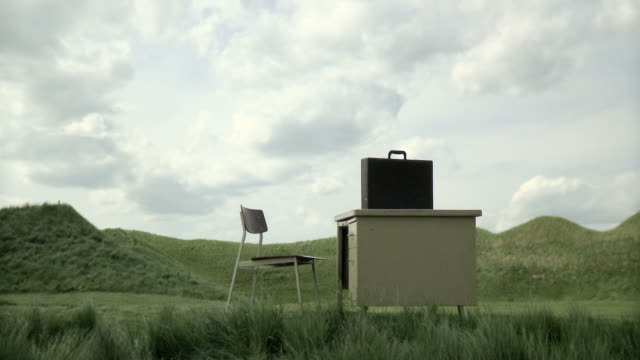 vídeos de stock, filmes e b-roll de a desk and a chair in a field with briefcase on desk - grupo pequeno de objetos