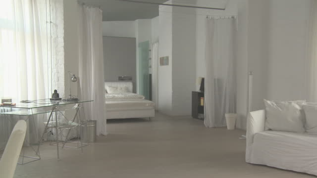 WS PAN Desk and bedroom area of loft decorated entirely in white/ Berlin, Germany