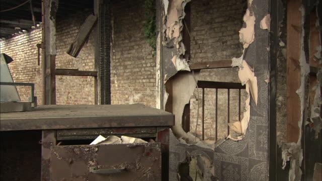 stockvideo's en b-roll-footage met a desk and chair are seen in a room of a derelict building. - verlaten slechte staat