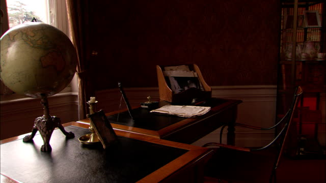 a desk in the home of jules verne holds a globe, a manuscript and a candle-holder among other things. - desk stock videos & royalty-free footage
