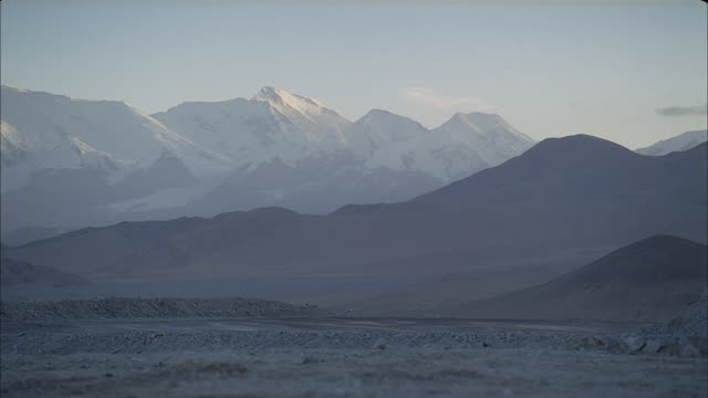 desolate hills stretch out to the snowcapped mountains in the horizon. - remote location stock videos & royalty-free footage