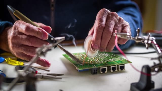 desoldering components from a circuit board - electrical equipment stock videos & royalty-free footage