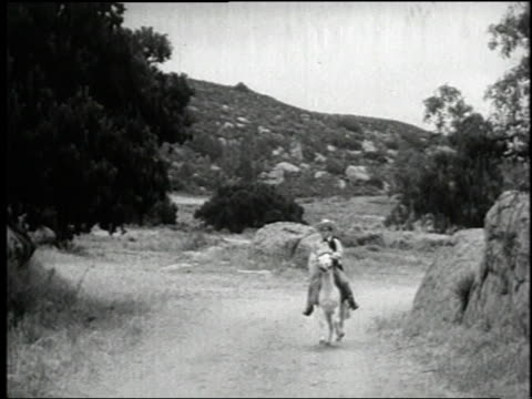 vídeos de stock e filmes b-roll de 1938 montage desperadoes ambushing the sheriff in the film 'terror of tiny town' / united states - bandido