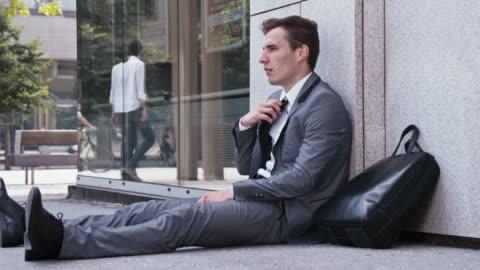 stockvideo's en b-roll-footage met wanhopige zakenman zittend op de straat - werkloosheid