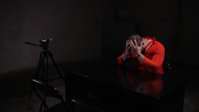 desperate male prisoner in orange jumpsuit sitting alone in interrogation room - prisoner orange stock videos & royalty-free footage