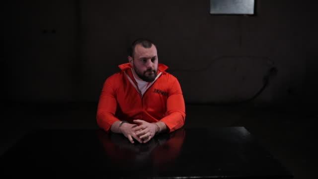 desperate male prisoner in sitting alone in interrogation room - prisoner orange stock videos & royalty-free footage