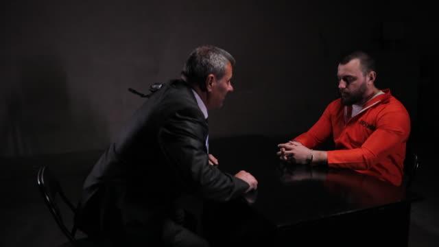 尋問室に一人で座っている絶望的な男の囚人 - 捕らわれる点の映像素材/bロール