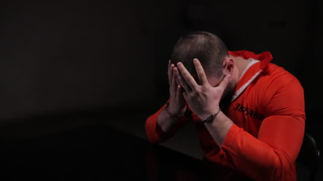 desperate prisoner in orange jumpsuit sitting alone in interrogation room - manette video stock e b–roll