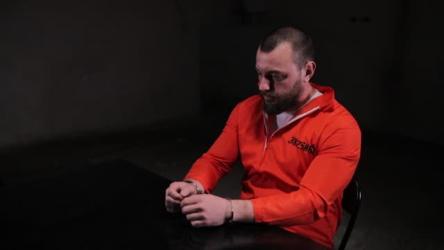 desperate prisoner in sitting alone in interrogation room - prisoner orange stock videos & royalty-free footage