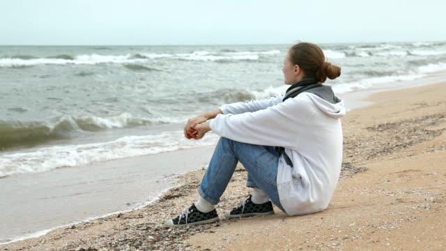 vidéos et rushes de désespérée jeune femme attendant quelqu'un à la mer - dépression terrestre