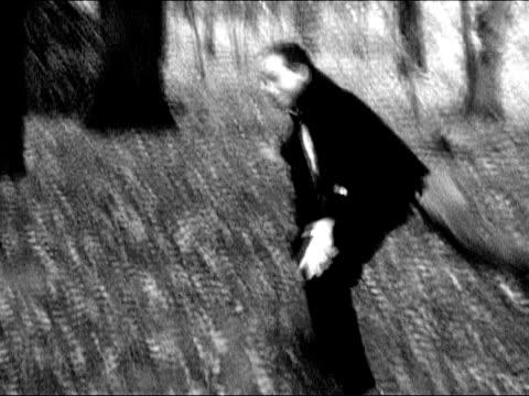 vidéos et rushes de desperated homme d'affaires de running pour sa vie forêt sombre - trébucher