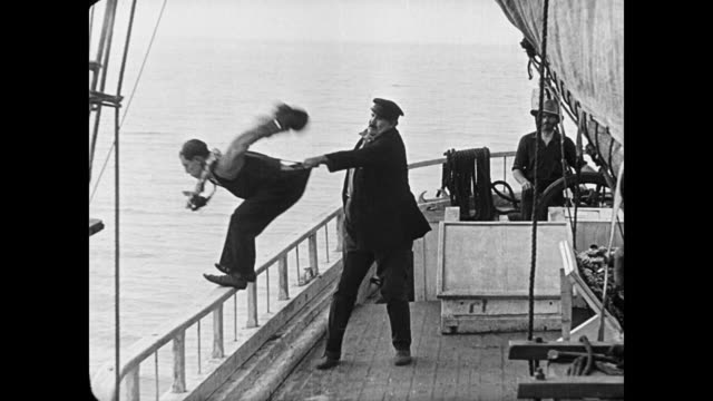 1923 despite pouring hot coffee into sea captain's (joe roberts) lap, resigned cabin boy (buster keaton) is not thrown overboard - suicide stock videos & royalty-free footage