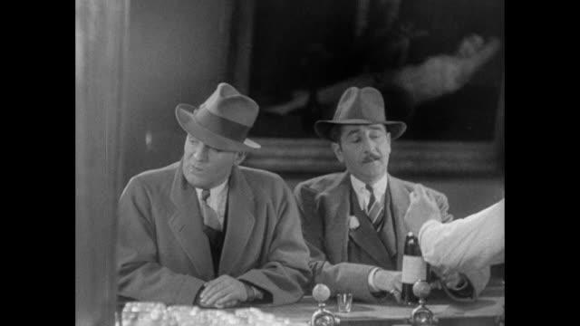 vídeos de stock, filmes e b-roll de 1931 despite reporter (pat o'brien) refusing drink, editor (adolph menjou) orders for them both - 1931