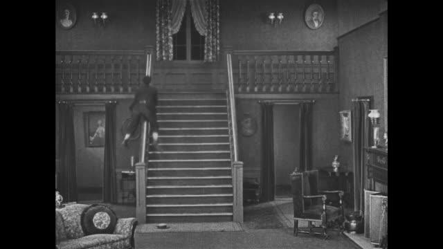 1921 despite sliding down banister, man (buster keaton) still slips on vanishing staircase - 1921 stock videos & royalty-free footage