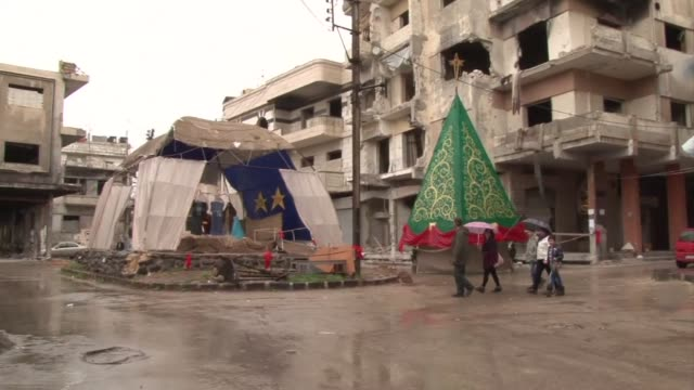 stockvideo's en b-roll-footage met despite the war christians in homs who were able to return to their neighborhood are preparing christmas in the ruins of the former capital of the... - voormalig