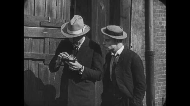 vídeos de stock e filmes b-roll de 1921 despondent man (buster keaton) loses lucky horse shoe to passing man who happily finds wallet - sorte