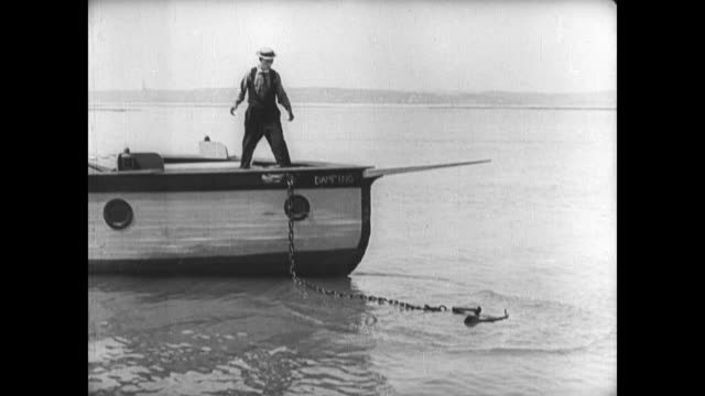 1921 despondent man (buster keaton) watches his boat's anchor float on water's surface - 1921年点の映像素材/bロール